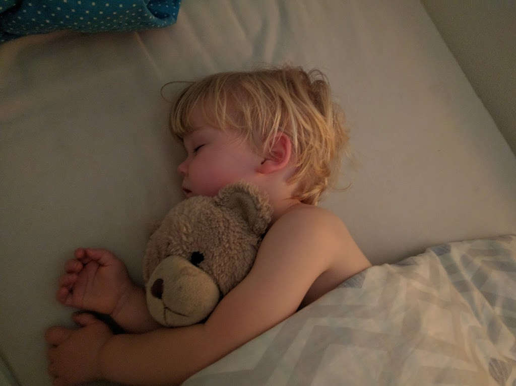 Boy sleeping with his teddy in bed