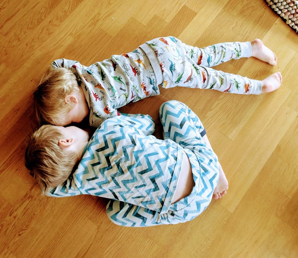 Two boys in pyjamas lying on the floor and talking